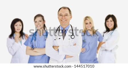A group of confident doctors and nurses with their arms crossed displaying some attitude and smiling isolated on a white background - stock photo