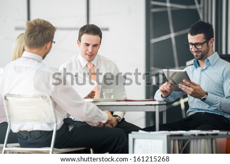 A group of corporate people working by the office table