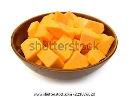 A group of cut and slice butternut squash chunks in bowl on a white background.  - stock photo