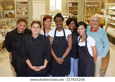 A group of deli workers standing in their shop - stock photo