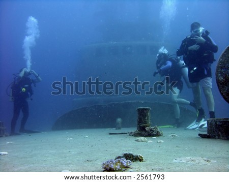 A group of divers that's just landed on the deck of a ship. - stock photo