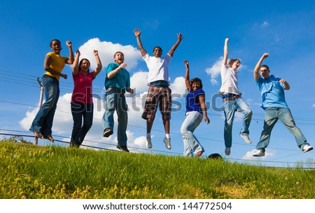 A group of diverse college students/friends jumping in the air outside on a hill