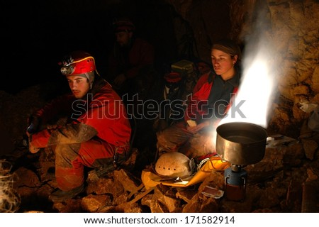 A group of explorers resting in a cave bivouac - stock photo