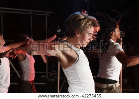 A group of female and male freestyle hip-hop dancers during dance training session on stage. Lit with spotlights. Movement on edges of dancers