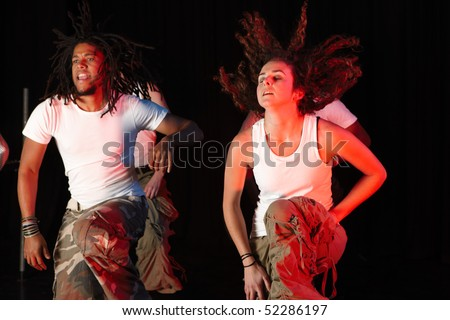 A group of female and male freestyle hip-hop dancers during dance training session on stage. Lit with spotlights