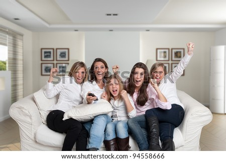 A group of  female family members sitting at home cheering - stock photo