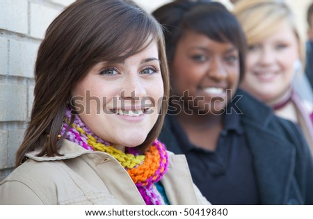 A group of female multi-racial college students/friends outside against a brick wall - stock photo
