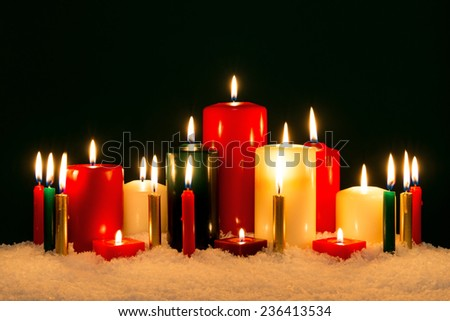 A group of festive candles in snow burning against a black background.