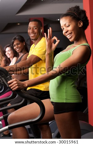 a group of fit friends doing cardio with the woman in the front giving the okay sign with her hand - stock photo