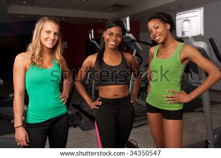 a group of fit friends poses near cardio equipement - stock photo