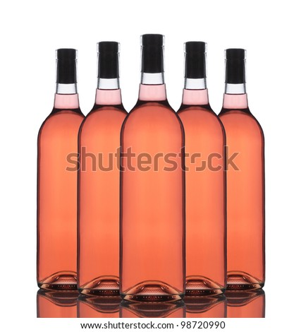 A Group of five Blush wine bottles without labels on a white background with reflection. - stock photo