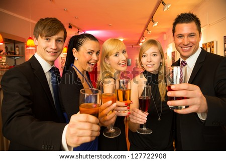 A group of five friends celebrating in a bar and posing for the camera - stock photo