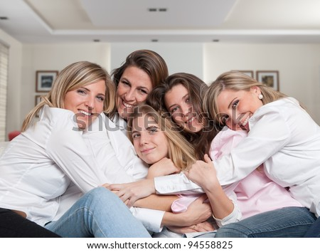 A group of five happy women of different ages hugging in the living room - stock photo