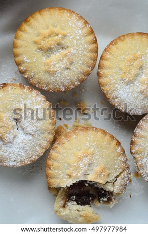 A group of four Christmas mince pies, shot from above, with one broken open to expose filling.