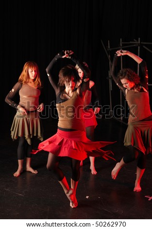 A group of four female freestyle hip-hop dancers in a dancing training session. Lit with spotlights. Movement on edges of dancers