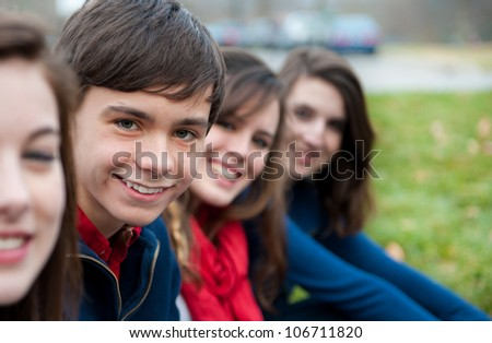 A group of four happy teenagers outside - stock photo
