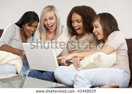 A group of four interracial beautiful young women having fun looking at something surprising and funny on their laptop computer and laughing - stock photo