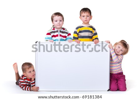 A group of four kids are holding a big white bord; isolated on the white background - stock photo