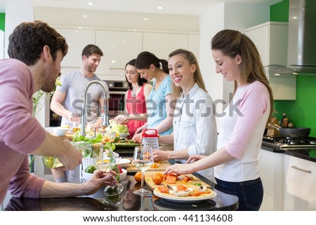 A group of friends are preparing a meal together in the kitchen - stock photo