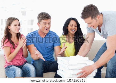 A group of friends celebrate as a man brings them some pizza