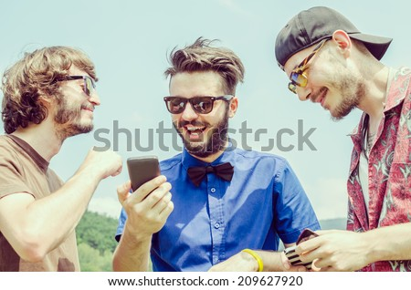 A group of friends chatting with their smartphones - stock photo