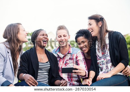 A group of friends chatting with their smartphones