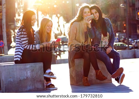 A group of friends having fun with smartphones in the street - stock photo