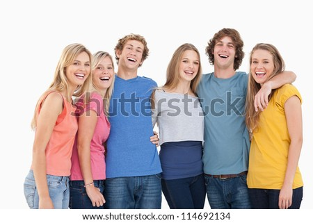 A group of friends holding each other and smiling while looking into the camera - stock photo