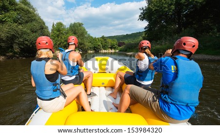 A group of friends in an inflatable raft moving down a river - stock photo
