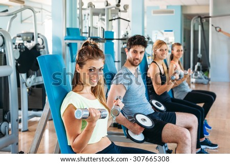 A group of friends in sportswear (three women and a man), they are training in the fitness room of a gym sitting on benches exercising with weights handlebars - stock photo