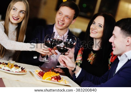 a group of friends in the restaurant celebrates
