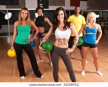 a group of friends poses in a gym after a class - stock photo