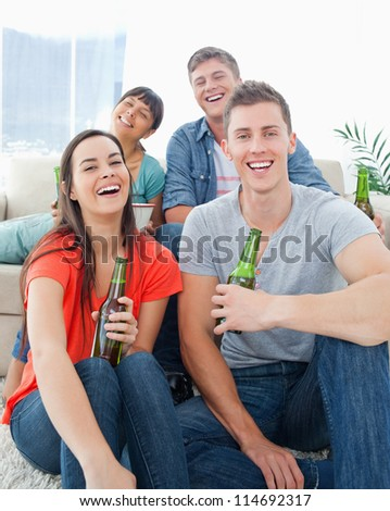 A group of friends sitting on the couch and the floor as they hold beers in their hands while laughing