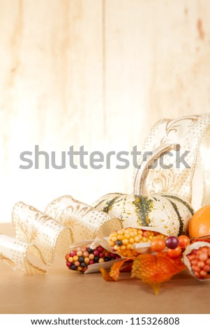 A group of gold and orange fall items sit against a wooden background. - stock photo