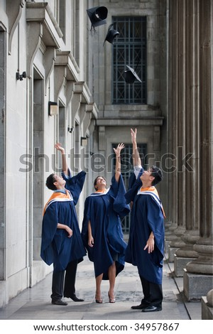 A group of graduates toss their mortar boards into the air in a hallway - stock photo