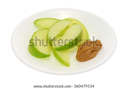 A group of green apple slices on a dish with a small amount of peanut butter for dipping isolated on a white background. - stock photo