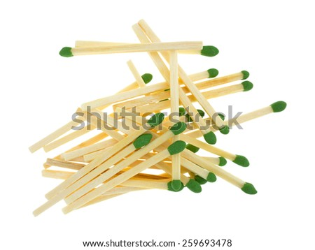 A group of green sulfur tipped matchsticks in a jumble on a white background. - stock photo