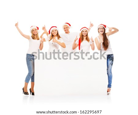 A group of happy and emotional teenagers in Christmas hats posing near a large blank banner