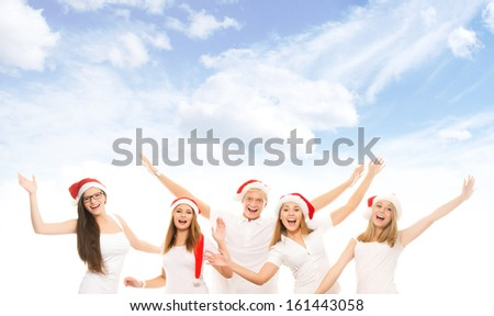 A group of happy and emotional teenagers in Christmas hats posing over heaven background - stock photo