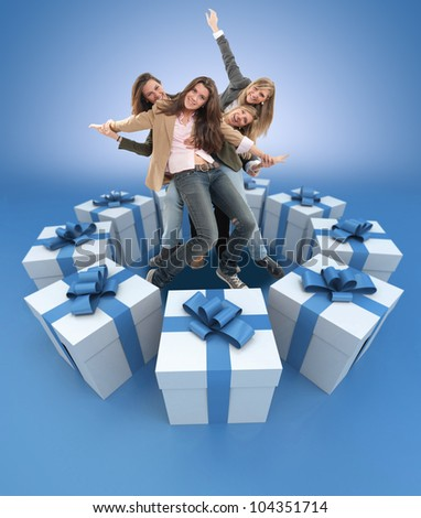 A group of happy celebrating women surrounded by gift boxes