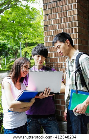 A group of Happy smiling students standing together with books at a campus - stock photo
