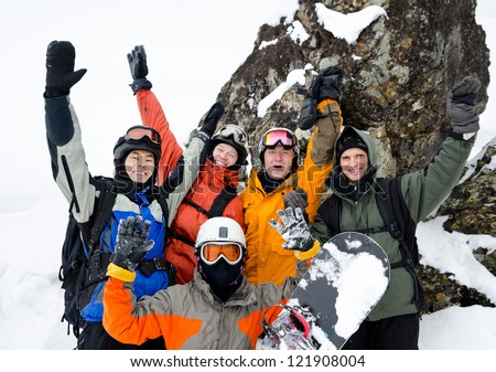 a group of happy snowboarders high in mountains - stock photo