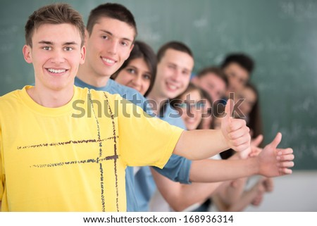 A group of happy students showing thumbs up in a row - stock photo