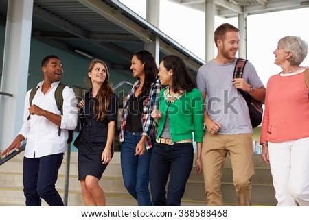 A group of happy teachers walking in a school corridor - stock photo