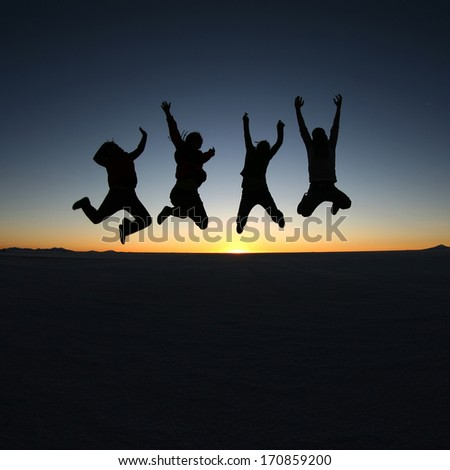 A group of happy young friends jumping in Solar de Uyuni, Bolivia - stock photo