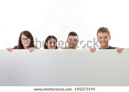 A group of happy young people isolated on white leaning on an empty banner