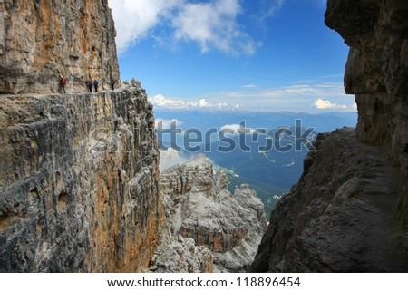 "A group of hikers going ""via ferrata"" along the rock edge - Dolomiti mountains, Dolomiti di Brenta, Italy - stock photo"