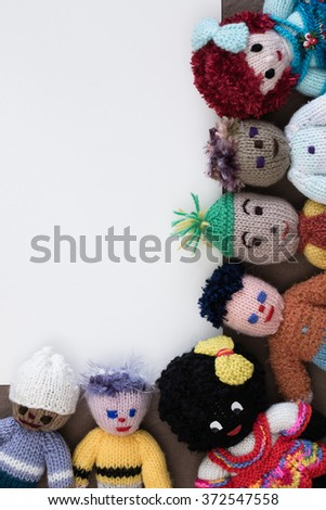 A group of homemade yarn children with pencils, a ruler around white paper creating a border for multicultural ideas and concepts. Can be used as a vertical or horizontal, copy space, flat lay