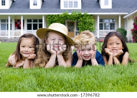A group of kids laying in the grass. Diveristy and friendship