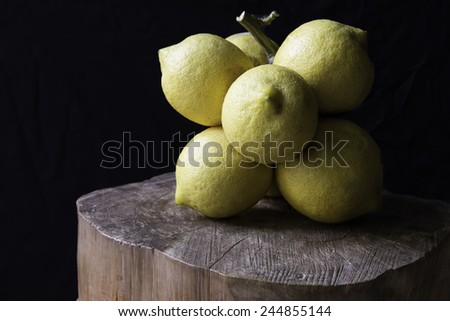 A group of lemons, strangely born together on the same branch, is standing on a wooden cut trunk, on black background.  - stock photo